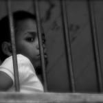 Bambino dietro la finestra con sbarre