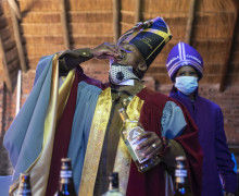 Tsietsi Makiti (L) the founder and leader of Gabola church drinks a shot of gin during the Sunday sermon at Bunny's Tavern in Evaton on August 30, 2020. - Gabola church was founded three years ago by Tsietsi Makiti to capture the unchurched people that would ordinarily be rejected by conventional traditional and pentecostal/evangelical churches that frown on imbibers. This Sunday's service was held at Bunny's Tavern in the working class suburb of Evaton, 50 kilometres south of Johannesburg.It was held to celebrate the end of the ban on alcohol sales in South Africa. (Photo by WIKUS DE WET / AFP)